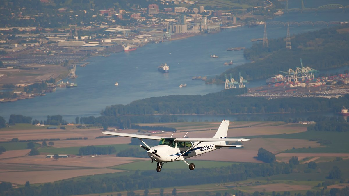 Cessna flying along Columbia River